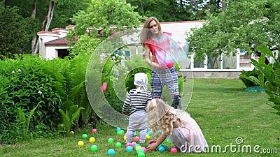 Kaukasische familie die buitenshuis speelt met kleurrijke ballen Gimbal-bewegingsschot stock video