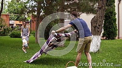 Kaukasische familie in openlucht Vader, moeder en weinig blondy zoon De papa spreidt een picknickdekking, picknickmand uit Groen  stock videobeelden