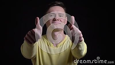 Kaukasische mens op middelbare leeftijd in het gele sweater gesturing vinger-op tekens als en opzicht in camera op zwarte te tone stock footage