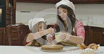 Kaukasische moeder en dochter die gecondenseerde melk op gebakken cake aanbrengen Fijne familie in kookhoeden en aprons die koken stock video