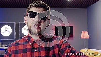 Kaukasischer Mann spricht und klatscht dynamisch im Raum mit belichteten Kühlvorrichtungen stock video footage