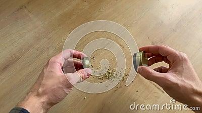 Kaukasiska manliga händer som mala medicinska marijuana i en liten guldkvarn arkivfilmer