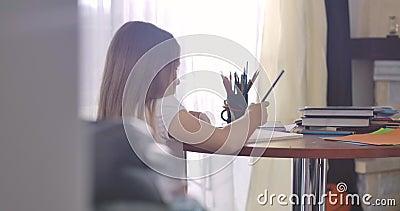 Kaukaska dziewczyna z długimi włosami siedząca w słońcu i licząca na palce i zapisująca wyniki Inteligentny zbiory wideo