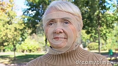 Kaukaska emeryta kobieta siedząca w parku, spokojna wieś wypoczynkowa, starsze pokolenie zbiory