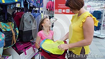 Kaukaski matki i córki blisko sklep odkłada wybierać szkolnej torby plecaka w pasamonictwo rynku zdjęcie wideo