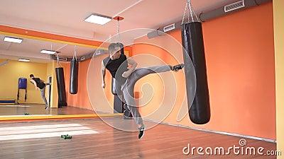 Kaukaski samiec mistrz sporty w sztuka samoobrony, kopie uderza pięścią torbę w gym, samoobrony szkolenie, zwolnione tempo zbiory wideo