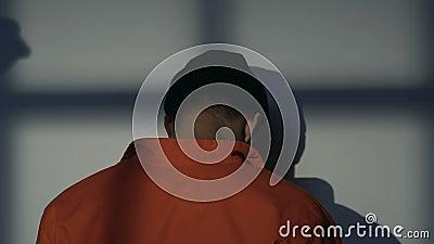 Kaukaski więzień obracający ściana, strażowy cień z batutą w rękach, napad zbiory wideo