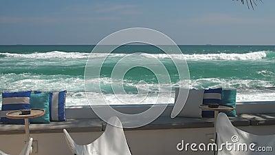 Kawiarnia z stołami przeciwko pięknemu, azurowemu, powolnemu ruchowi oceanu zbiory
