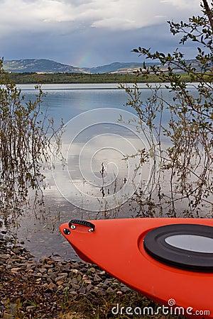 Kayak on shore in willow bushes alongside a lake