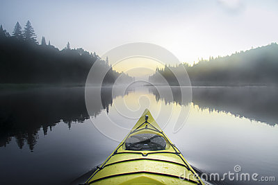 Kayak surfer on a misty lake