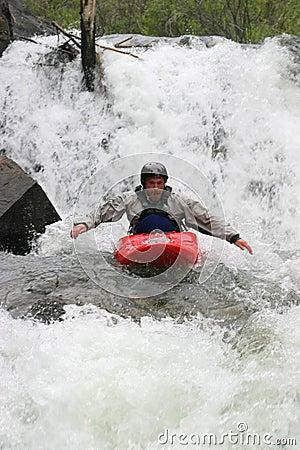 Kayaker hand paddling waterfall