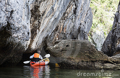 Kayaker Paddling through Caves