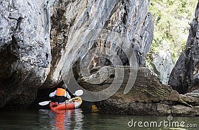 Kayaker Paddling through Caves