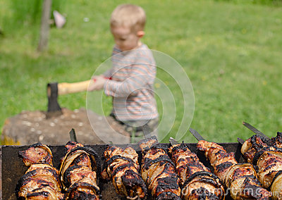 Kebabs grilling on a BBQ as a small boy chops wood Stock Photo