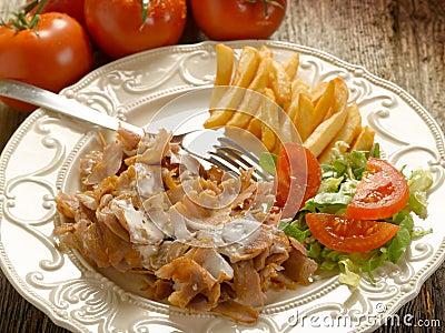 Kebap con la ensalada y las patatas encendido