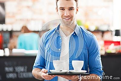 Kellner mit Kaffee auf Behälter