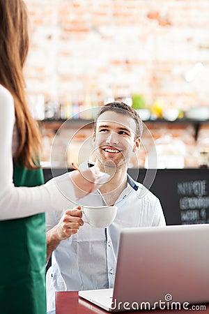 Młody człowiek słuzyć przy kawiarnią