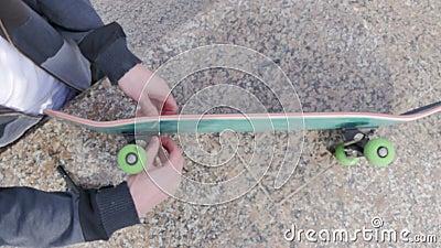Kerl verdreht Bolzen in das Skateboard stock footage