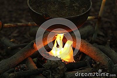 A kettle pot over a campfire.