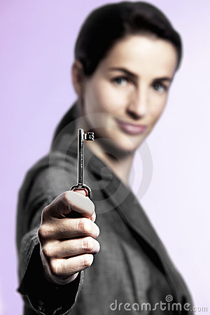 Key to success, business woman holding key upright