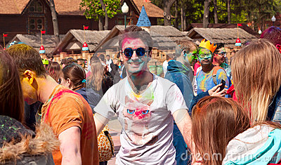 Kharkiv, Ukraine - April 24, 2016. Portrait of a painted guy among people at the Holi festival Editorial Stock Image