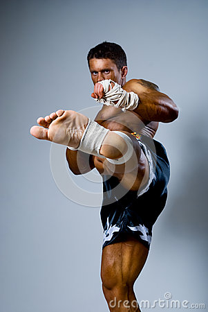 Kick-boxer kicks on a gray background.