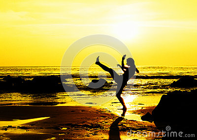 Kick boxing young woman on the beach Stock Photo