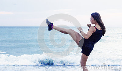 Kick boxing young woman working out on the beach Stock Photo