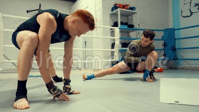 Kickboxer dois que estica os pés ao preparar-se para lutar o treinamento no anel video estoque