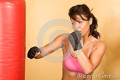 Kickboxing training, woman in kicking Punching Bag