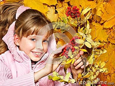 Kid in autumn orange leaves.