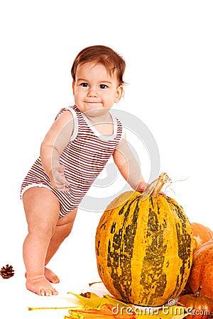 Kid beside autumnal harvest