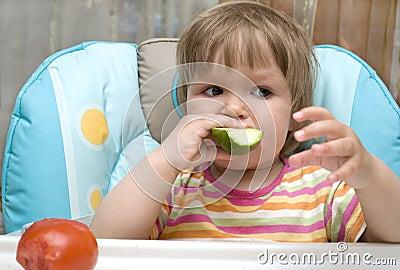 Kid is bite off cucumber