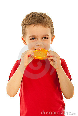Kid boy biting slice orange