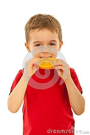 Kid boy biting slice orange