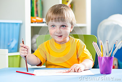 Kid boy draws with pencils indoors Stock Photo