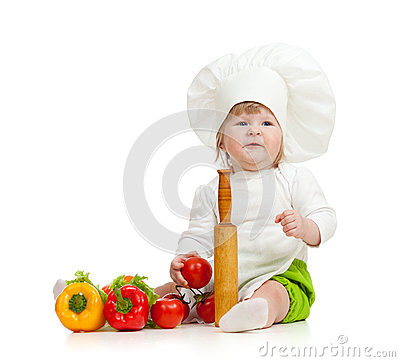 Kid in chef hat with healthy food vegetables