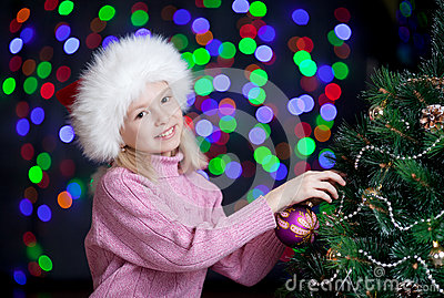 Kid decorating Christmas tree on bright backdrop