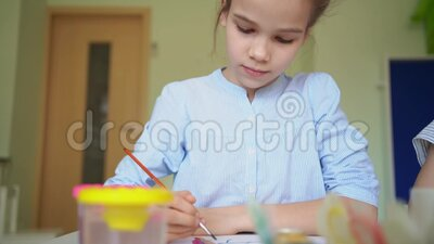 Kid drawing with brush and paints. At the centre for studies of children stock footage