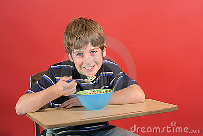 Kid eating cereal at desk