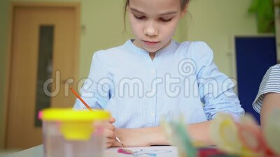 Kid girl drawing with brush and paints. At the centre for studies of children stock footage