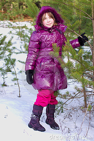 Kid girl posing in a winter forest