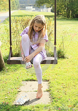 Free Kid - Girl Putting On Shoes On Swing Royalty Free Stock Images - 45677489