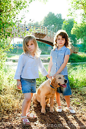 Kid girls with Golden retriever puppy outdoor