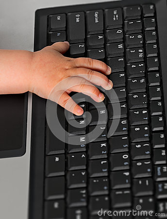 Kid hand on a laptop keyboard