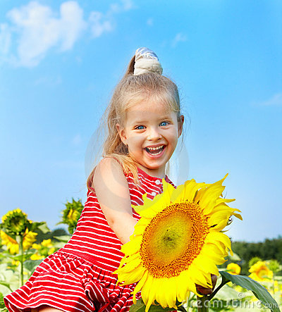 Kid holding sunflower outdoor.
