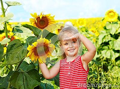Kid holding sunflower outdoor.