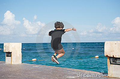 Kid jumping into the ocean