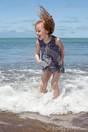 Kid jumping in the ocean waves