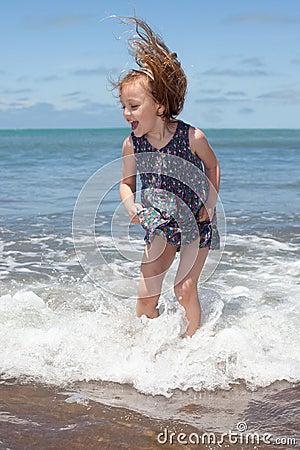 Kid jumping in the ocean waves